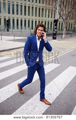 Full length portrait of a young businessman talking on his mobile phone while walking in the street