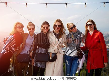 Large group of smiling girlfriends staying together at sunny day and looking at camera