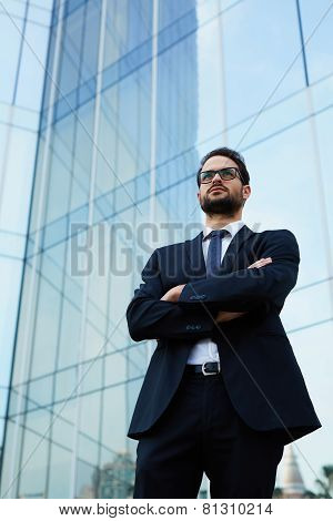 Confident businessman with crossed arms standing against skyscraper building