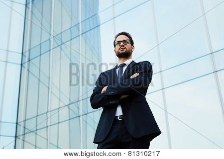 Portrait of a confident young businessman in glasses standing with crossed arms