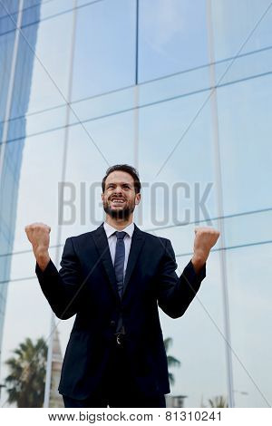 An excited man with celebrating success businessman with his arms raised standing near office buildi