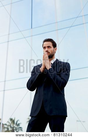Young businessman standing with palms together and rested against his mouth