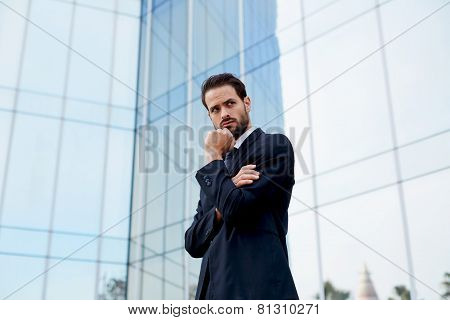 Portrait of serious pensive business man standing with arm crossed and hand against his mouth
