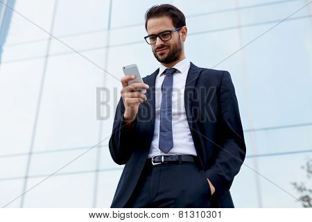 Portrait of handsome businessman looking at cell phone standing near office