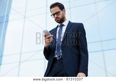 Portrait of worried young business man looking to his cell phone standing near office building