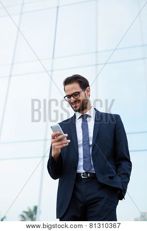 Half length of happy businessman reading text message on cell phone with one hand in a pocket