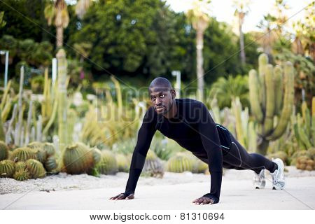 Fit man working out in the park doing push-ups