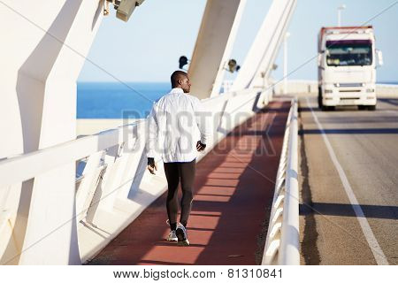 Full length portrait of walking runner while he resting after intensive training outdoors