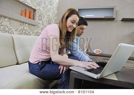 Young Couple Working On Laptop At Home