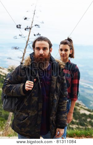 Portrait of beautiful young couple of hikers standing with a backpacks in the outdoors