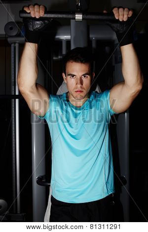 Young athletic man with muscular body doing pull up exercise in gym