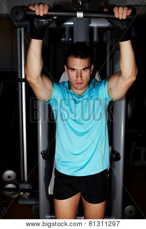 Portrait of attractive man doing exercise on pulls ups machine at gym