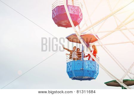 A group of young active women have fun while turning on the big ferris wheel