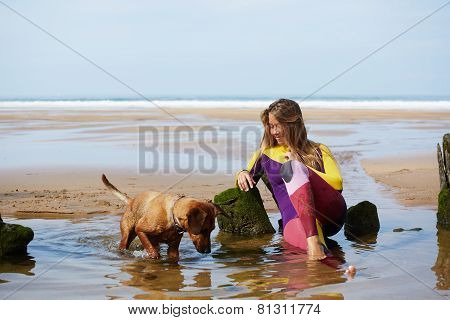 Professional surfer girl taking a break sitting against the ocean young surfer girl in wets suit