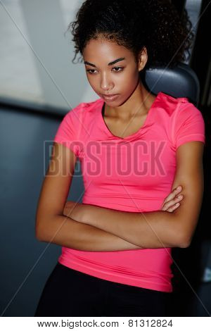 Portrait of fit woman with crossed arms relaxing after fitness training at gym