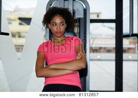 Portrait of fit athletic woman leaning on press machine while having a rest after workout