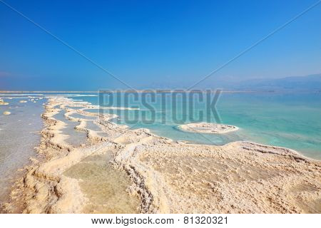 Israel in October. Freakish patterns of the evaporated salt in the Dead Sea. Salt formed long paths with scalloped edges