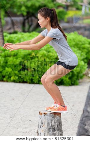 Fitness woman athlete bench jump squat jumping outside in nature landscape. Strength training fit girl working out exercising outdoors on beach in summer doing jumping on tree trunk.