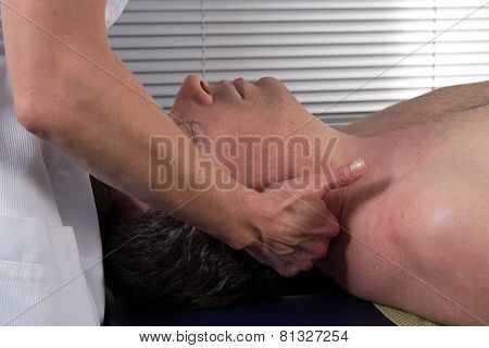A Man Is Getting A Massage On His Neck And His Head