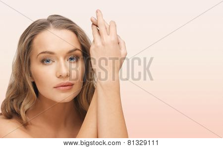 people, beauty, body and skin care concept - beautiful woman face and hands over pink background