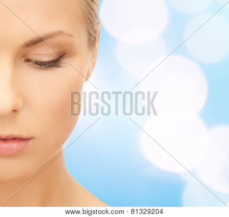 beauty, people and health concept - beautiful young woman face over blue lights background