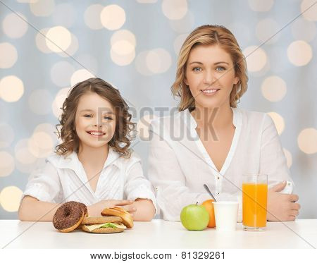 people, healthy lifestyle, family and unhealthy food concept - happy mother and daughter eating different food over holidays lights background