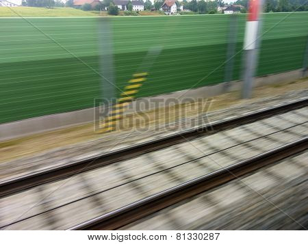 tracks and rails out in motion from a moving train. symbolic photo for train, tempo and dynamics