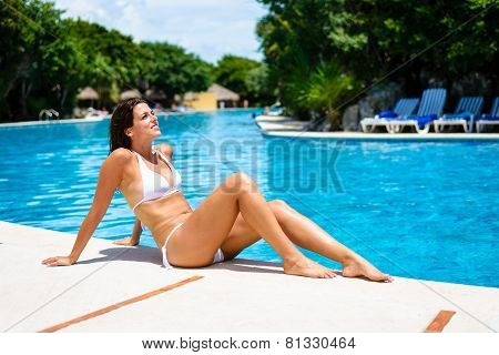 Young Woman Sunbathing And Relaxing At Resort Swimming Pool