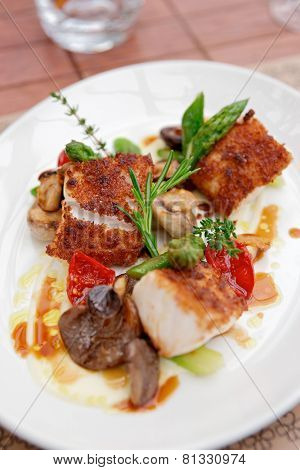 Coalfish fillet with mushrooms and asparagus on plate