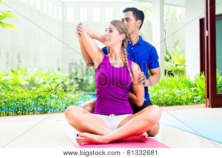 Fitness woman with personal trainer exercising, mixed Asian and Caucasian couple
