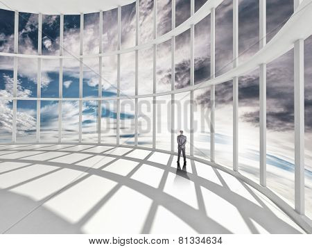 businessman standing in office and looking at sky in window
