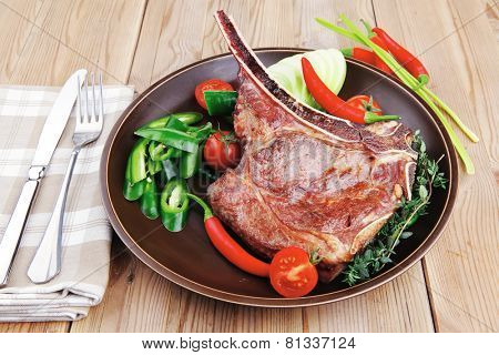 savory : roasted beef spare rib on dark dish with cutlery thyme pepper and tomato on wooden table