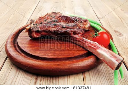 served main course: grilled pork ribs served with green chives and cherry tomato on wooden plate