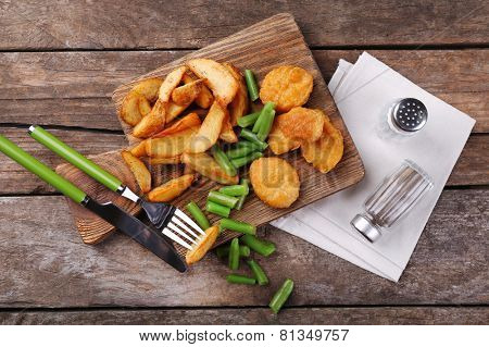 Breaded fried chicken nuggets and potatoes with asparagus on catting board and wooden planks background