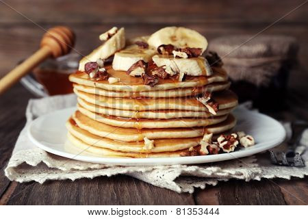 Stack of delicious pancakes with chocolate, honey, nuts and slices of banana on plate and napkin on wooden background