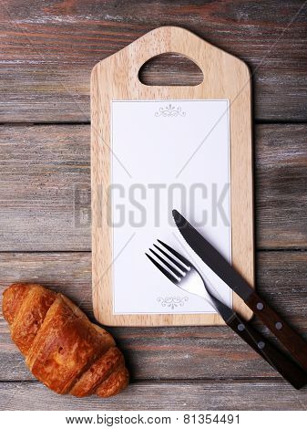 Cutting board with menu sheet of paper and croissant on rustic wooden planks background