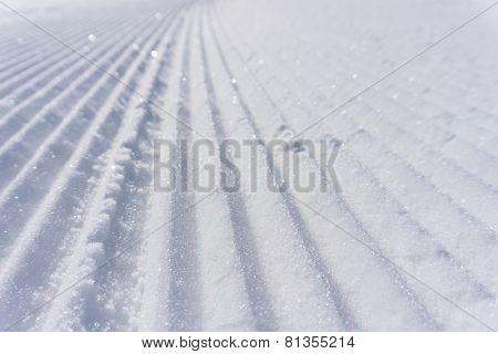 Fresh snow groomer tracks on a mountain ski piste, background