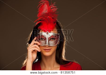 Beauty Portrait Of Beautiful Young Blonde Woman With Venice Carnival Mask In Hands Over Orange Backg
