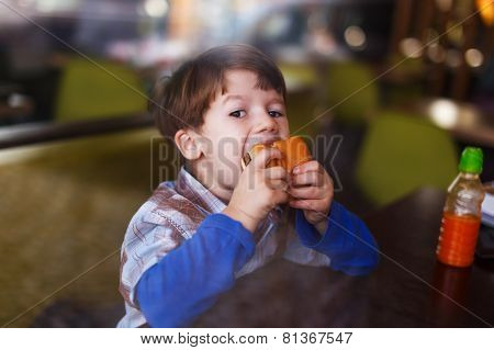 Little Boy Eat Burger Behind Glass