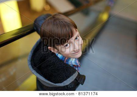 Little Boy Looking Back On Escalator