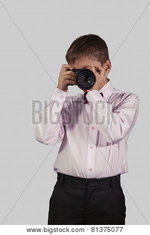 Half-length Portrait Of A Boy With A Camera In The Face On A Gray Background