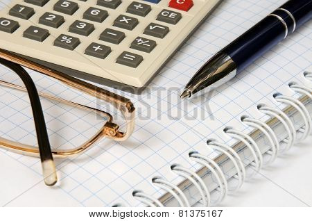 Calculator, glasses, pen and notebook