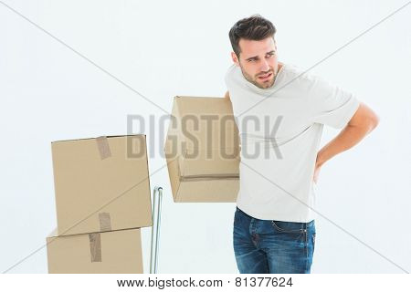 Upset delivery man with cardboard boxes suffering from backach on white background
