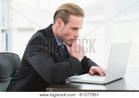 Focused businessman in suit using laptop in his office