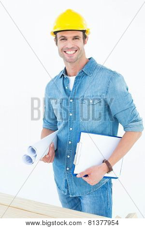 Portrait of happy carpenter holding rolled blueprint and clipboard over white background