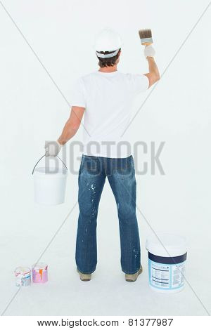 Full length rear view of man using paintbrush on white background