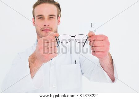 A optician showing glasses next to an eye test on white background