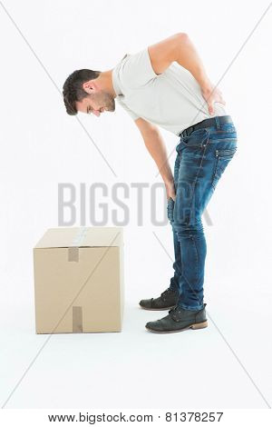 Full length side view of delivery man suffering from back pain on white background