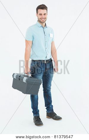 Full length portrait of confident male technician carrying toolbox on white background