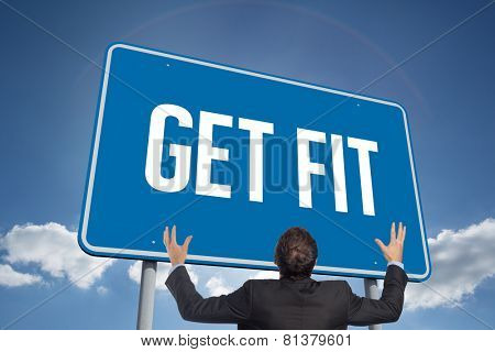 The word get fit and gesturing businessman against cloudy sky with sunshine